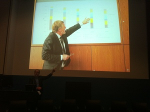 A German presenter gets in the way of the graph that Adam Bandt MP intended to photograph. Adam is the small, dark pointer at the front of the slide.